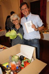 Brigitte Rühl-Preitler und Hans Preitler mit einem Grundnahrungsmittelpaket vor ihnen und dem Buch mit Rezepten in der Hand. Foto: E.Ertl