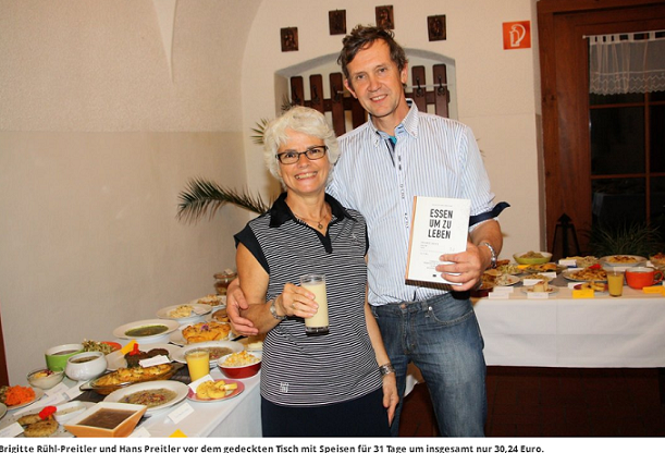 Brigitte Rühl-Preitler und Hans Preitler stehen vor einem vollen Tisch mit Speisen für 31 Tage.