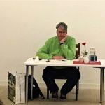 """Inklusionsbotschafter Birger Höhn sitzt ganz entspannt an einem Tisch, vor Beginn seiner Lesung zum Buch """"Innenansicht eines Menschen mit Autismus"""""""